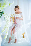 Pregnant girl in a white lace dress sitting in the interior with flowers and hugs belly Stock Photos
