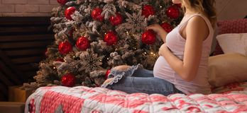 A pregnant girl in a white T-shirt and jeans is sitting on the bed near the New Year tree, a gift for the new year stock photo