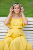Pregnant girl in a yellow dress clothes headphones Royalty Free Stock Photos