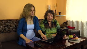 Pregnant granddaughter woman help grandmother with computer stock video