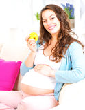 Pregnant happy woman eating apple royalty free stock photos