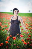 Pregnant happy woman in a flowering poppy field Royalty Free Stock Photography