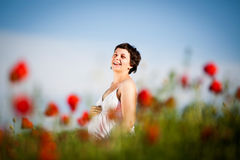 Pregnant happy woman in a flowering poppy field Stock Photo