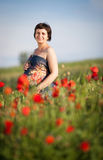 Pregnant happy woman in a flowering poppy field Stock Photography