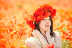 Pregnant happy woman in a flowering poppy field outdoors Stock Image