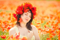 Pregnant happy woman in a flowering poppy field outdoors Stock Images