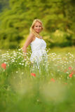 Pregnant happy woman in a flowering poppy field outdoors Stock Photo