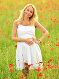 Pregnant happy woman in a flowering poppy field outdoors Royalty Free Stock Photos