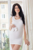 Pregnant happy woman is holding baby's bootees Stock Photography