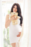 Pregnant happy woman is holding teddy bear Stock Image