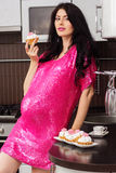 Pregnant happy woman in kitchen eating cakes Royalty Free Stock Image