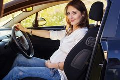 Pregnant happy young woman is sitting in black car Stock Photos
