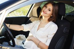 Pregnant happy young woman at the wheel of her car Royalty Free Stock Image