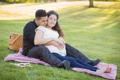 Pregnant Hispanic Couple in The Park Outdoors Royalty Free Stock Photo