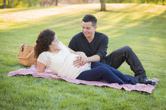 Pregnant Hispanic Couple in The Park Outdoors Royalty Free Stock Image
