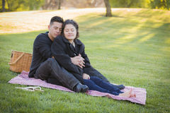 Pregnant Hispanic Couple in The Park Outdoors Stock Photo