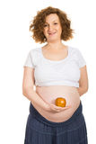 Pregnant holding apple in front of belly Stock Photos