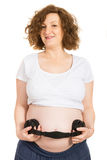 Pregnant holding headphones on her tummy Royalty Free Stock Photos
