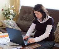 Pregnant home worker. Pregnant woman working at home with laptop Stock Photography