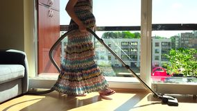 Pregnant house wife with big tummy hoover vacuum clean home stock video