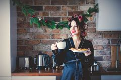 Pregnant housewife in bathrobe cup and cookies at kitchen stock photography
