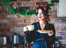 Pregnant housewife in bathrobe cup and cookies at kitchen. In Christmas time royalty free stock photography