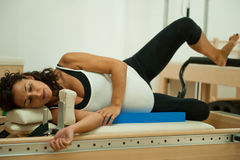 Pregnant lady doing pilates. Beautiful young pregnant lady doing pilates in her last week before delivery Royalty Free Stock Photography