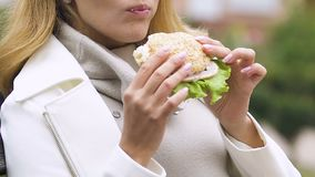 Pregnant lady eating burger with ham and fresh salad healthy appetite, lunchtime. Stock footage stock footage