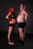 Pregnant lady with fat man. Young pregnant lady wearing the red scarf with her fat friend royalty free stock photos