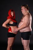 Pregnant lady with fat man. Young pregnant lady wearing the red scarf with her fat friend stock photos
