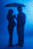 Pregnant lady and husband standing under a rain Royalty Free Stock Image