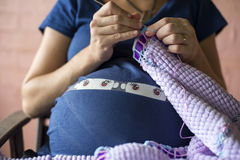 Pregnant lady knitting 02. Lady pregnant with twins knitting blanket Royalty Free Stock Photo