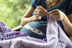 Pregnant lady knitting 01 Royalty Free Stock Image
