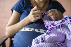 Pregnant lady knitting 03. Lady pregnant with twins knitting blanket Royalty Free Stock Images