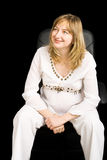 A pregnant lady sitting on a black chair stock photography