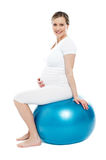 Pregnant lady sitting on exercise ball stock image