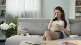 Pregnant lady sitting on sofa crying drying tears with tissue, hormonal disorder. Stock footage stock footage