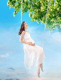 Pregnant lady sitting on the wooden swing Stock Photos