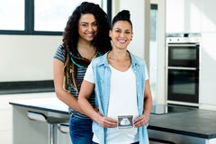 Pregnant lesbian couple holding a sonography report. And smiling in kitchen royalty free stock photos