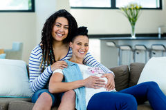 Pregnant lesbian couple with a pair of pink baby shoes. Pregnant lesbian couple sitting on sofa with a pair of pink baby shoes Stock Photos