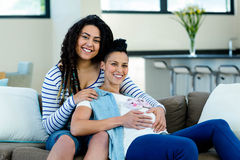 Pregnant lesbian couple with a pair of pink baby shoes. Pregnant lesbian couple sitting on sofa with a pair of pink baby shoes royalty free stock photography