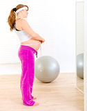 Pregnant looking in mirror and measuring her belly Royalty Free Stock Image