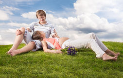 Pregnant lying on lawn with her husband Stock Photos