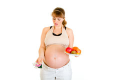 Pregnant making choice between pills and fruits Stock Photos