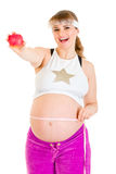 Pregnant measuring her belly and holding apple Royalty Free Stock Photos