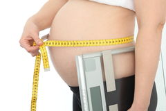 Pregnant with measuring tape and level Stock Photography