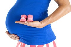 Pregnant model holding pink girl booties close up Stock Images