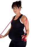 Pregnant model working out with a jump rope Royalty Free Stock Photos