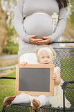 Pregnant Mom Behind Baby Girl in Chair Holding Blank Blackboard Stock Image
