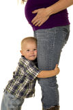 Pregnant mom in boots young boy hug her legs close Stock Photo